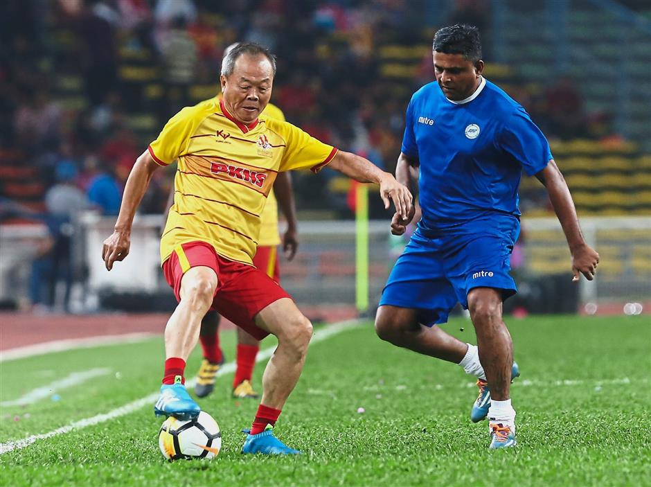 Selangor Veterans captain Chin Aun (left) in the thick of action with Singapores E. Manimohan during their match.