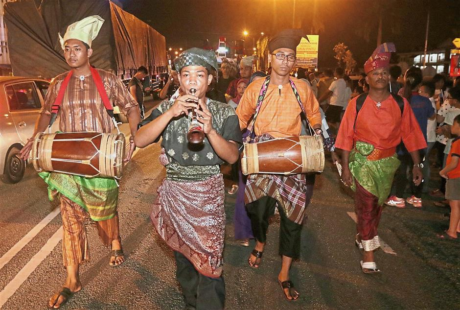 A troupe adding cultural variety to the celebration with traditional Malay music.