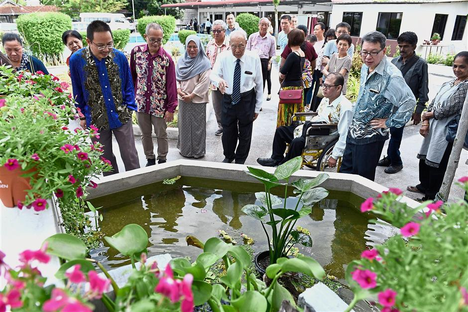Khoo (with tie) explaining the concept of the organic garden to the guests at Penang Cheshire Home.
