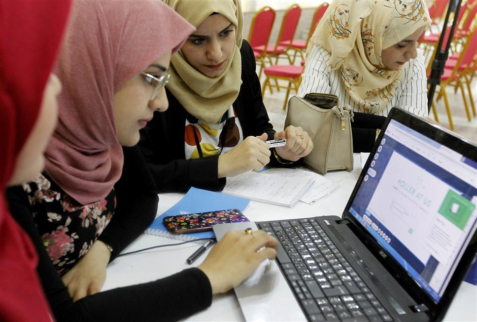 Iraqi girls check a computer at 'The Station', Baghdad's incubator for would-be entrepreneurs, in the Iraqi capital on November 17, 2018. - Stuck between an endless waitlist for a government job and a frail private sector, Iraqi entrepreneurs are taking on staggering unemployment by establishing their own start-ups. The first murmurs of this creative spirit were felt in 2013, but the Islamic State group's sweep across a third of the country the following year put many projects on hold. Now, with IS defeated, co-working spaces and incubators are flourishing in a country whose unemployment rate hovers around 10 percent but whose public sector is too bloated to hire. (Photo by SABAH ARAR / AFP)