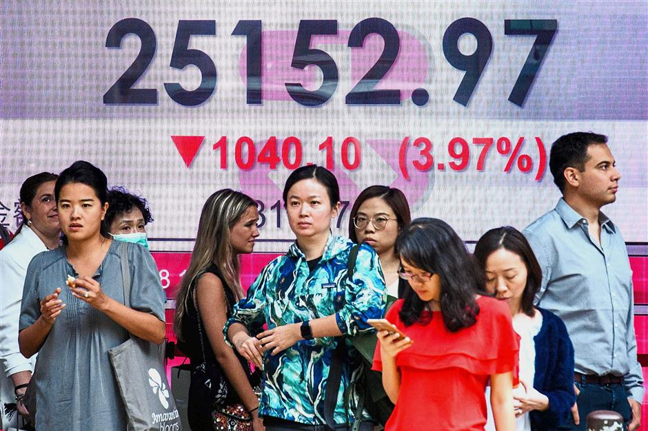 Market rout: Pedestrians stand in front of a stock display board that shows the Hang Seng Index at 25152.97, down 3.97 in Hong Kong on Thursday. Asian markets plunged Thursday morning following the worst session on Wall Street for months, as US President Donald Trump said the Federal Reserve had 'gone crazy' with plans for higher interest rates. — AFP