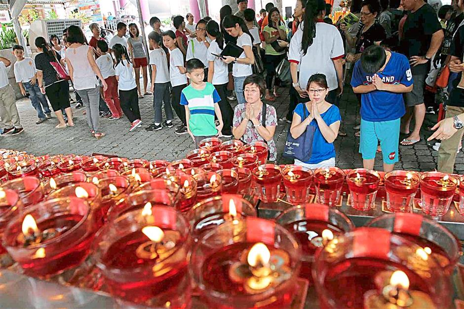 Devotees offering prayers at the oil lamps lighted for Wesak Day