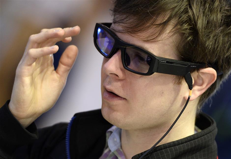 A young man tries new Vuzix Blade augmented reality smart glasses Prosumer on the first day of the Mobile World Congress (MWC) on February 26, 2018 in Barcelona. The Mobile World Congress, the world's biggest mobile fair, is held in Barcelona from February 26 to March 1.  / AFP PHOTO / Josep LAGO