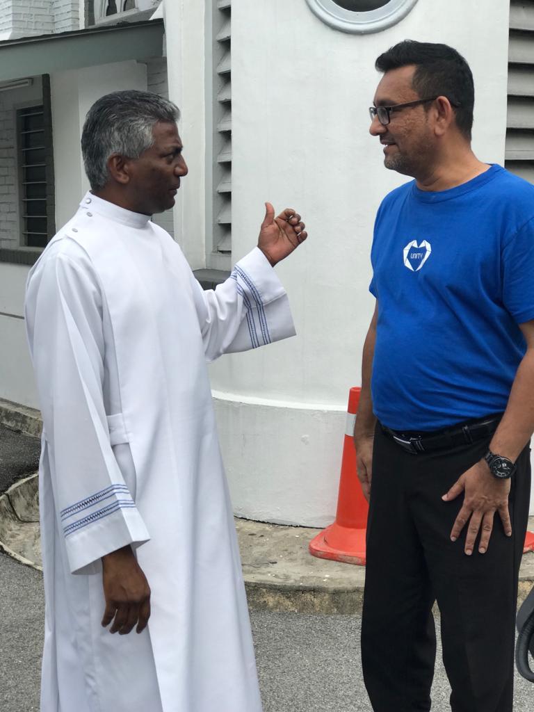 Shah Kirit speaking to Fr George Packiasamy during the visit.