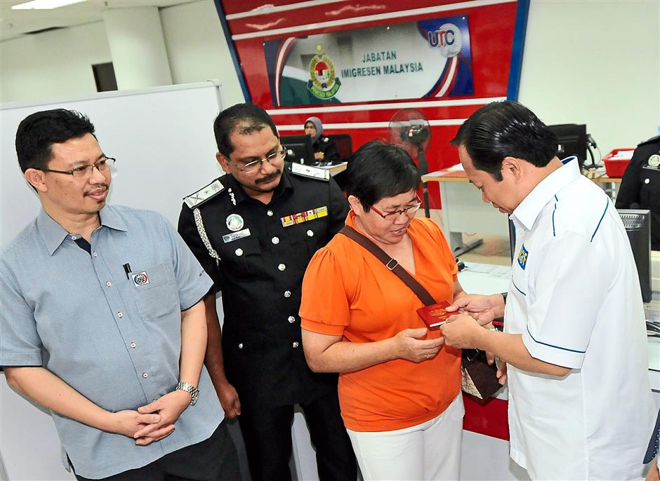 Here is your passport madam: Ahmad presenting a passport to Wang Mui Kiow during his working visit to the Johor Baru UTC at Galeria Kotaraya. Looking on are Johor Corp's president and chief executive Datuk Kamaruzzaman Abu Kassim (left) and Johor Immigration Department director Rohaizi Bahari (second from left).