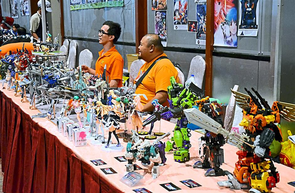 Combiner Transformers (far right, front), Macross and Gundam mecha share the limelight with their anime human co-stars on the same table during AniManGaki 2014 at Sunway Pyramid Convention Centre.