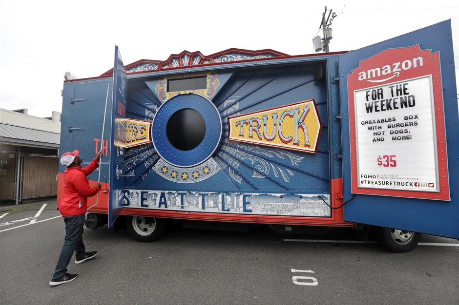 In this May 24, 2018, photo Amazon worker Khayyam Kain begins to open an Amazon Treasure Truck at a parking lot in Seattle. The Treasure Truck is a quirky way for the online retailer to connect with shoppers in person, expand its physical presence and promote itself. Amazon has also used the trucks to try to bring people into Whole Foods, the grocery chain it bought last year. The trucks debuted two years ago and now roam nearly dozens of cities in the United States and England. (AP Photo/Elaine Thompson)