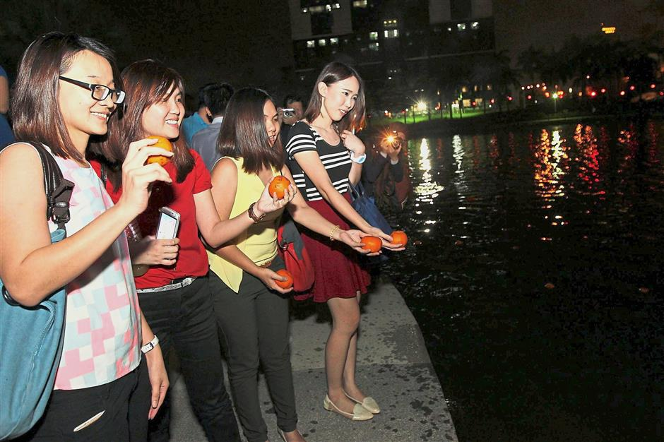 A group of women getting ready to toss mandarin oranges into the lake. — filepic