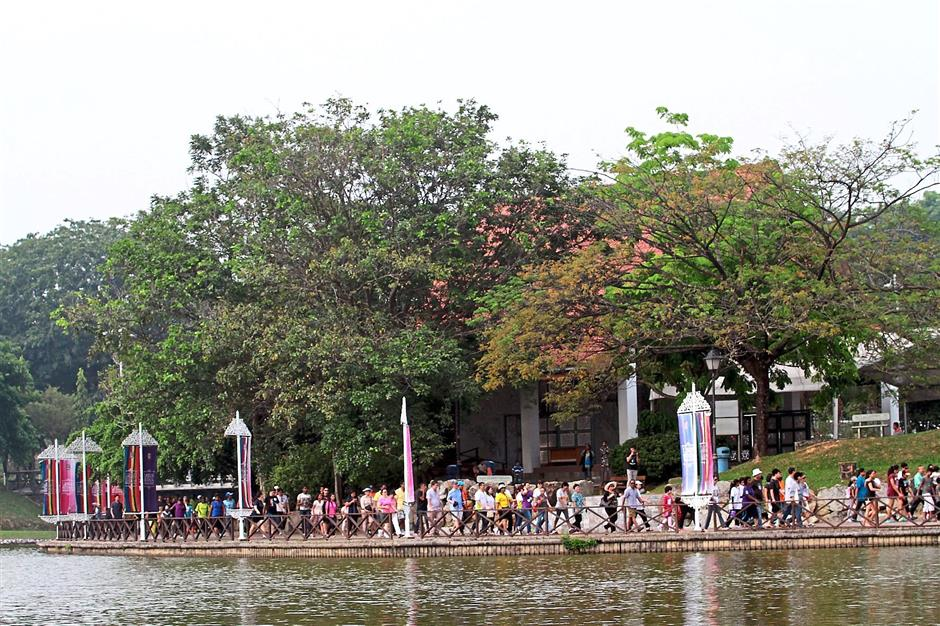 a peaceful walk.....the participants are walking across a bridge at the shah alam lake to mark the malaysia day celebration.
