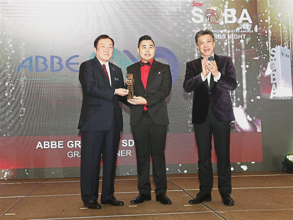 ABBE Group (M) Sdn Bhd managing director Dr Ho Wai Loon (centre) receiving the Rising Star Award from Ong (left) as Wong looks on.
