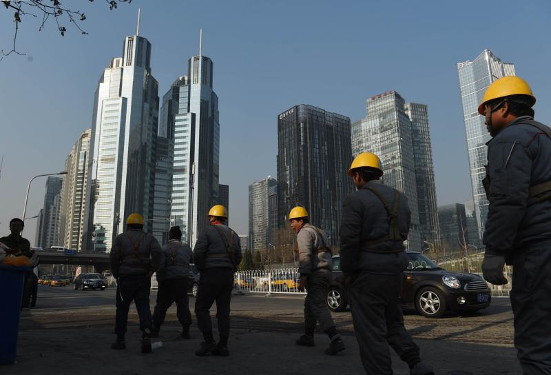 Workers walk back to a construction site after their lunch break in Beijing. The National Bureau of Statistics has revised up the estimated size of China\'s economy for 2013 by 3.4% to 58.8 trillion yuan (US$9.5tril) - AFP Photo.