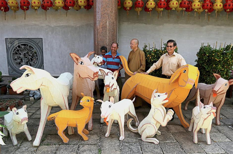 (From right) Ooi, Ven Xian Guan and devotees showing dog-shaped lanterns for the Chinese New Year celebration at Kek Lok Si Temple in Ayer Itam, Penang. — Photos: ZHAFARAN NASIB/The Star
