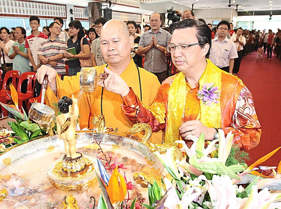 MCA president Datuk Seri Liow Tiong Lai (right) and Malaysian Buddhist Association (Kuala Lumpur/Selangor Branch) chairman Venerable Ming Ji (left) bathing the statue of Buddha during the Wesak Day celebration at Wisma Buddhist, Old Klang Road, Kuala Lumpur yesterday.SAMUEL ONG / THE STAR, 13TH MAY 2014.
