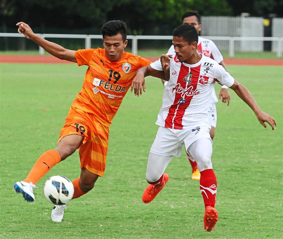 In control: KL Young Fighters' Muhammad Zul Fahmi (left) controlling the ball ahead of AirAsia All Stars' Mohamad Shaiful Nizam Saad.