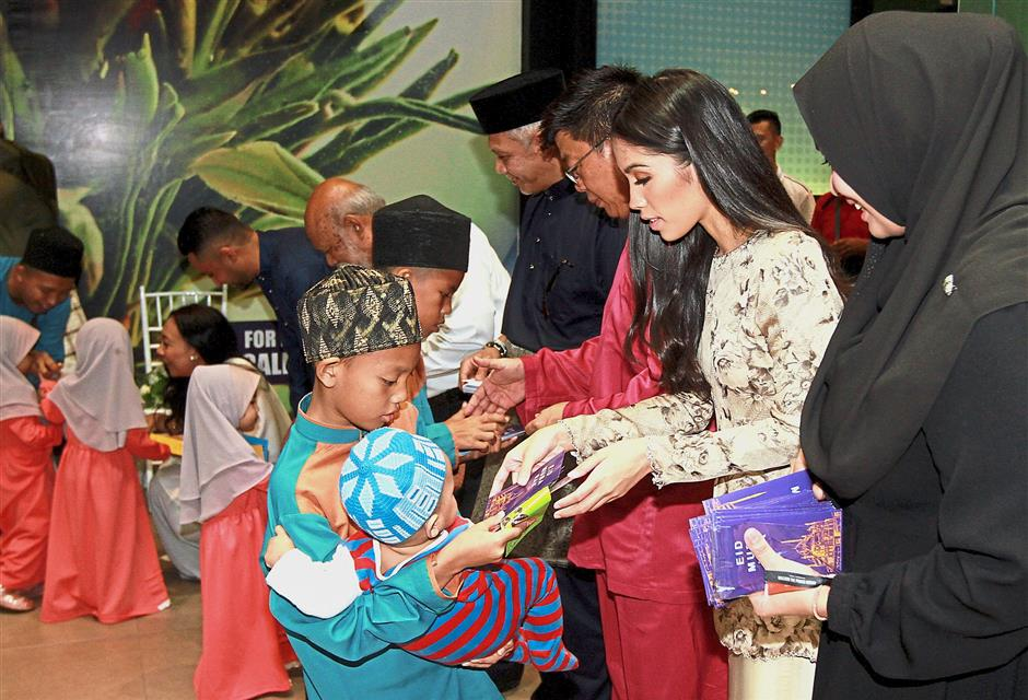 Tengku Puteri Iman (second from right) and Yeap (in pink) handing out duit raya to the children of Pusat Jagaan Budaya Harapan. — Photos: CHAN TAK KONG/The Star