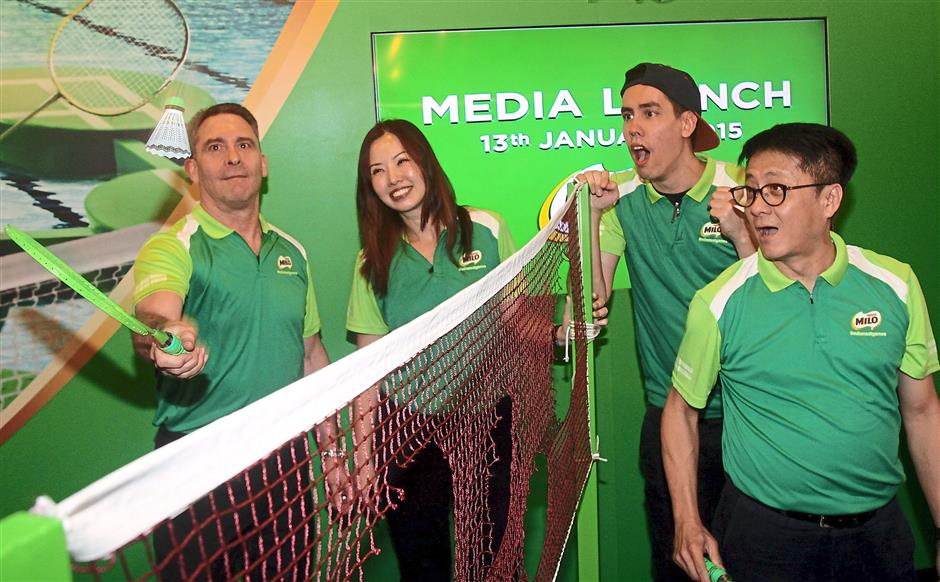 Interesting move: Nestle Malaysia head of shopper and consumer engagement Lester Kahn (left) and Nestle Malaysia communications director Khoo Kar Khoon having a go at a badminton game of their own rules as Wong (second from left) and radio announcer and emcee Ryan (second from right) cheer them on.