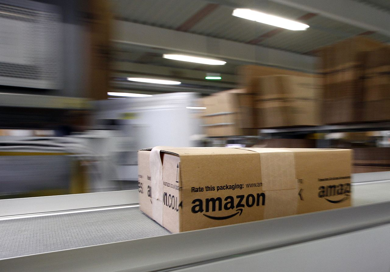 A parcel moves on the conveyor belt at Amazon's logistics centre in Graben near Augsburg December 16, 2013. Workers at Amazon.com's German operations were set to go on strike on Monday, in the middle of the crucial Christmas holiday season, in a dispute over pay that has been raging for months. The Verdi union said workers would strike in Amazon's logistic centres in Bad Hersfeld and Leipzig and, for the first time, in Graben. REUTERS/Michaela Rehle (GERMANY - Tags: BUSINESS EMPLOYMENT)