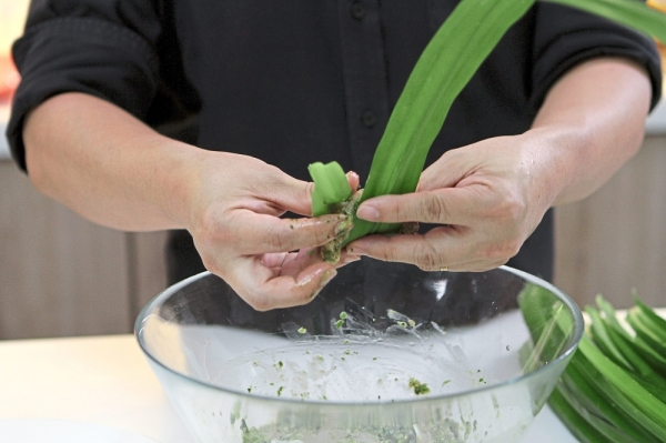 When the coconut milk has been absorbed into the chicken, begin wrapping the pieces in pandan leaves.