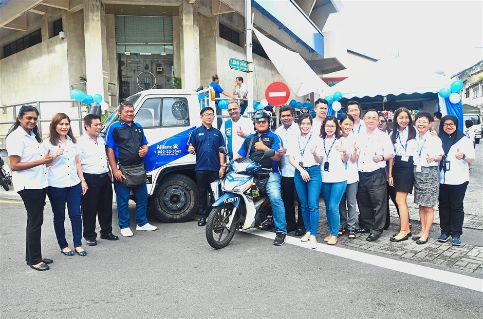Employees and road rangers of the Penang branch of Allianz General Insurance giving the thumbs-up during the launch.