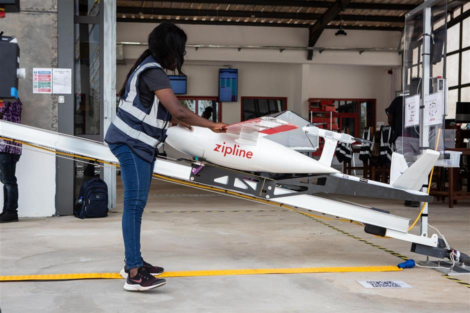 A staff member prepares a drone for the delivery of medical supplies at the drone delivery service base run by operator Zipline in Omenako, 70 kilometres (40 miles) north of Accra on April 23, 2019. - Ghana launched a fleet of drones on April 24, 2019 to carry medical supplies to remote areas, with Ghana's President declaring it would become the 'world's largest drone delivery service.' The craft are part of an ambitious plan to leapfrog problems of medical access in a country with poor roads. The drones have been flying test runs with blood and vaccines, but the project was officially inaugurated Wednesday at the main drone base in Omenako, 70 kilometres (40 miles) north of Accra. Operator Zipline, a US-based company, said the three other sites should be up and running by the end of 2019. The drones are planned to ferry 150 different medicines, blood, and vaccines to more than 2,000 clinics serving over 12 million people -- roughly 40 percent of the population. (Photo by Ruth McDowall / AFP)