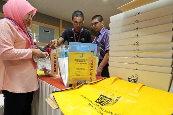 Important job: EC staff inspecting ballot boxes at SMJK Tiong Hua hall in Sandakan.