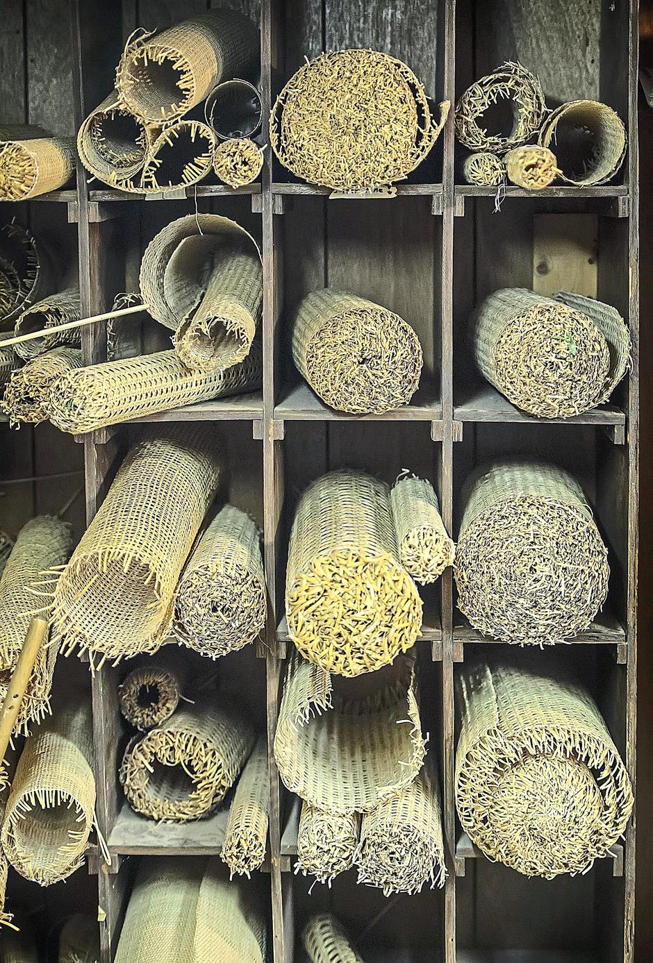 Rolls of pre-woven cane await chairs with grooves for installation.