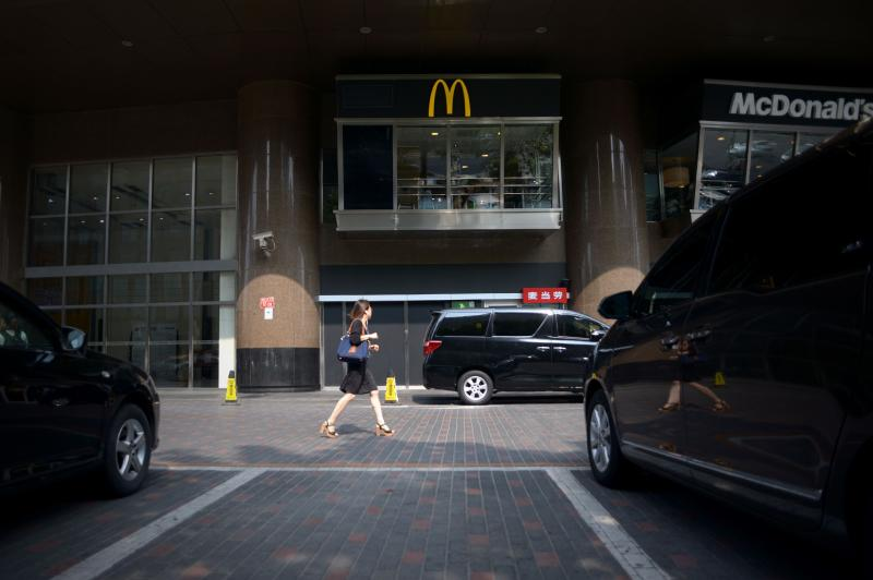 A woman walks past a McDonald\'s fastfood restaurant in Beijing on July 28, 2014. The use of expired meat and doctoring of food production dates by Shanghai Husi Food Co Ltd, which supply meat to McDonald\'s among others, has led to regulators immediately closing the factory, affecting the fast food chain\'s operations and outlook in EAst Asia - AFP Photo.