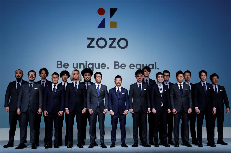 Yusaku Maezawa (C), the chief executive of Zozo, which operates Japan\'s popular fashion shopping site Zozotown and is officially called Start Today Co, poses with his employees who wear made-to-measure suits using skintight bodysuits which help customers upload their measurements online at an event launching the debut of its formal apparel items, in Tokyo, Japan, July 3, 2018. REUTERS/Kim Kyung-Hoon