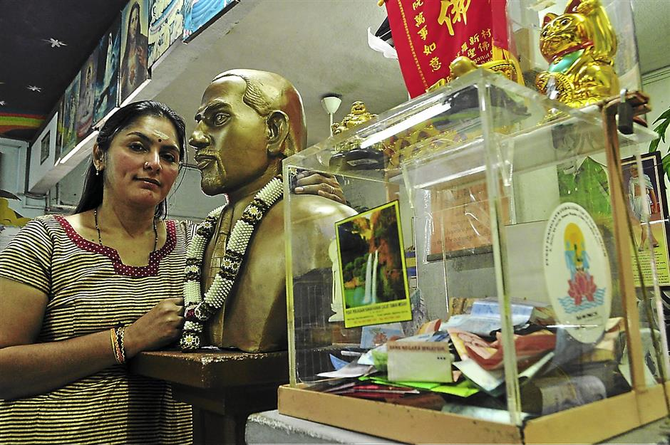 Umah, the president of the Taman Megah home stands next to a memorial bust of her late husband, Manikumar, who started the home