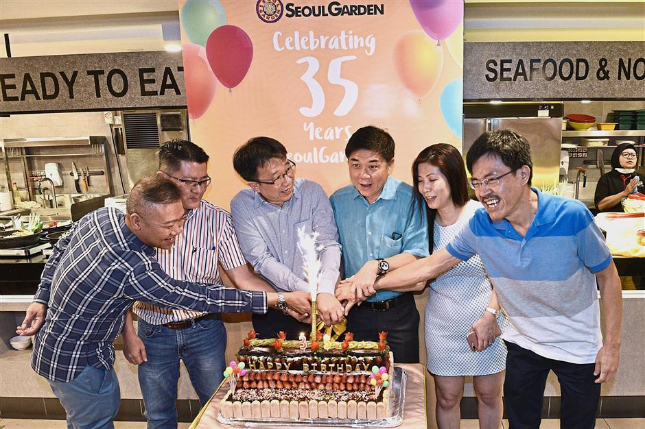 Siow (centre, light blue shirt) and Joseph (turquoise shirt) are joined by other senior management members during the cake-cutting ceremony to commemorate Seoul Garden's 35th anniversary celebration at its Gurney Plaza outlet. — Photos: GARY CHEN/The Star
