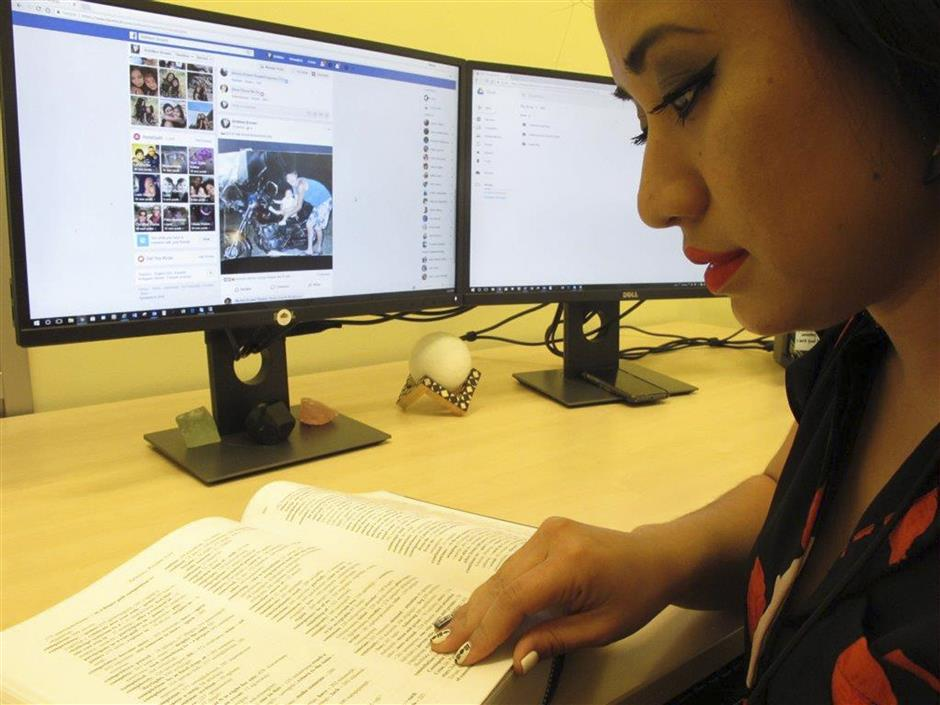 In this Thursday, Aug. 23, 2018 photo, Britt'Nee Brower interacts with the new Inupiat Eskimo language option now available for Facebook bookmarks, action buttons in Anchorage, Alaska. Alaskans made the option a reality through the social media giant's community translation tool. (AP Photo/Rachel D'Oro)