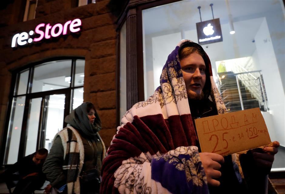 A man holds a sign about selling his place in line before the Apple\'s new iPhone XS and XS Max go on sale in front of a cell phone store in central Moscow, Russia September 26, 2018. REUTERS/Tatyana Makeyeva