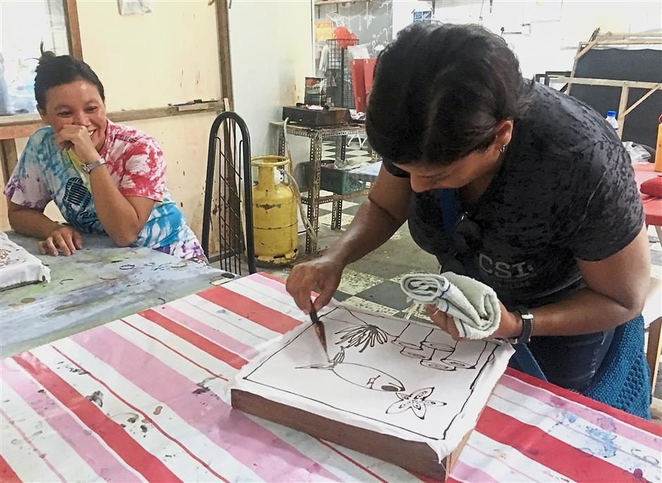 Wan Rozilawati watching my friend, Aida Ahmad, as she tries her hand at batik colouring.