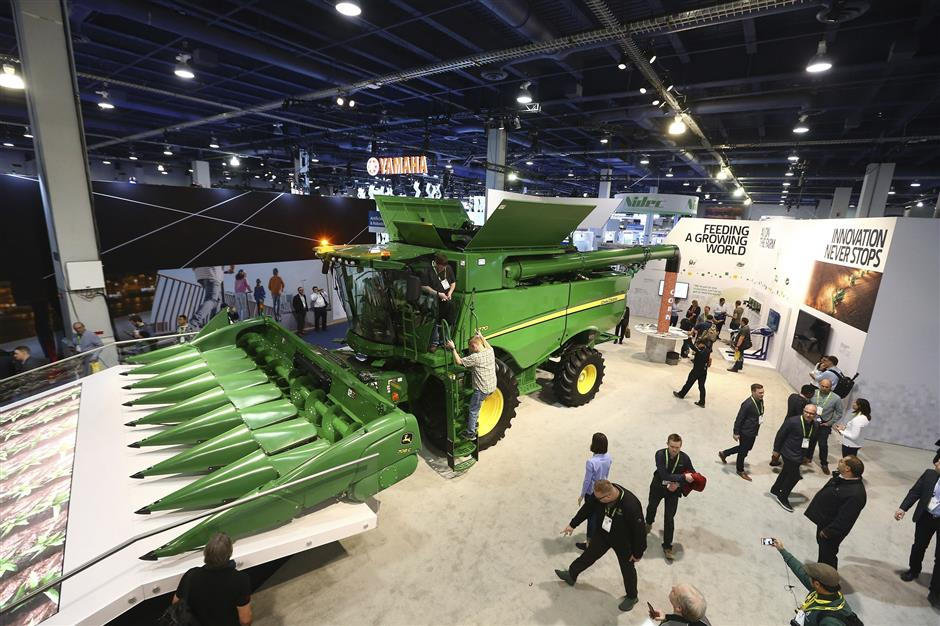 John Deere has hauled in a 20-ton combine harvester aided by artificial intelligence, while the combine has cameras with computer-vision technology to track the quality of grain coming into the machine so that its kernel-separating settings can be adjusted automatically, as farmers can monitor it remotely using a smartphone app, shown at CES International Tuesday, Jan. 8, 2019, in Las Vegas. (AP Photo/Ross D. Franklin)