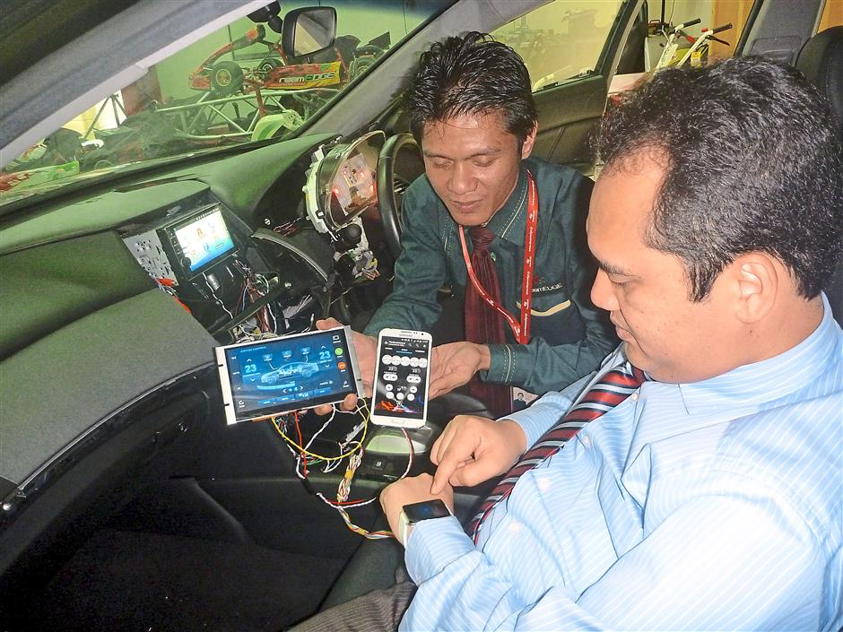 Khairil Adri Adnan (right) trying out the electronic functions of a car that can be controlled using wearable devices and smartphones.