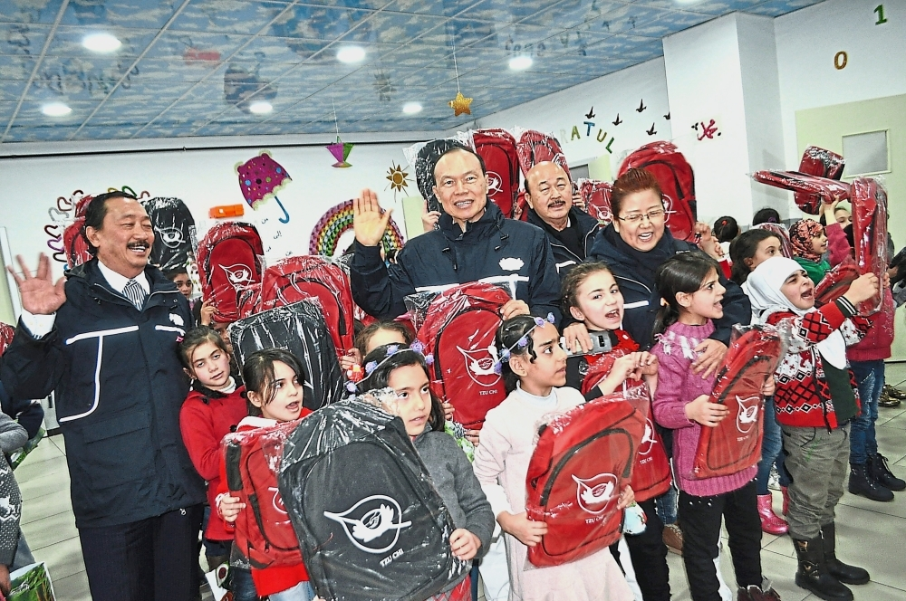 Tan (left), Lim (second left) and his wife Puan Sri Tong Siew Bee (first right) as well as Bina Puri Mining  executive chairman Datuk Yong Seng Yeow (second from right)  distributing school bags to Syrian  children at the El Menahil International School in Sultangazi.