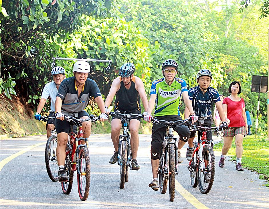 Cyclists can roll back downhill on the road after tackling the tough jungle trails of Bukit Kiara.