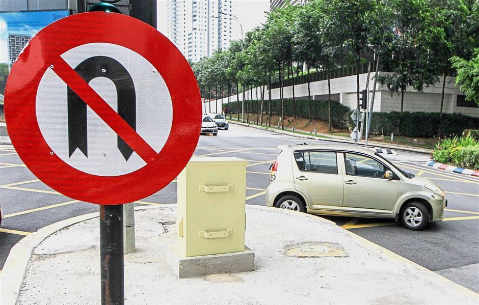A motorist is seen here attempting a U-turn at the Jalan Damansara - Jalan Wan Kadir 3 intersection, despite the no U-turn signs on both sides of the road.