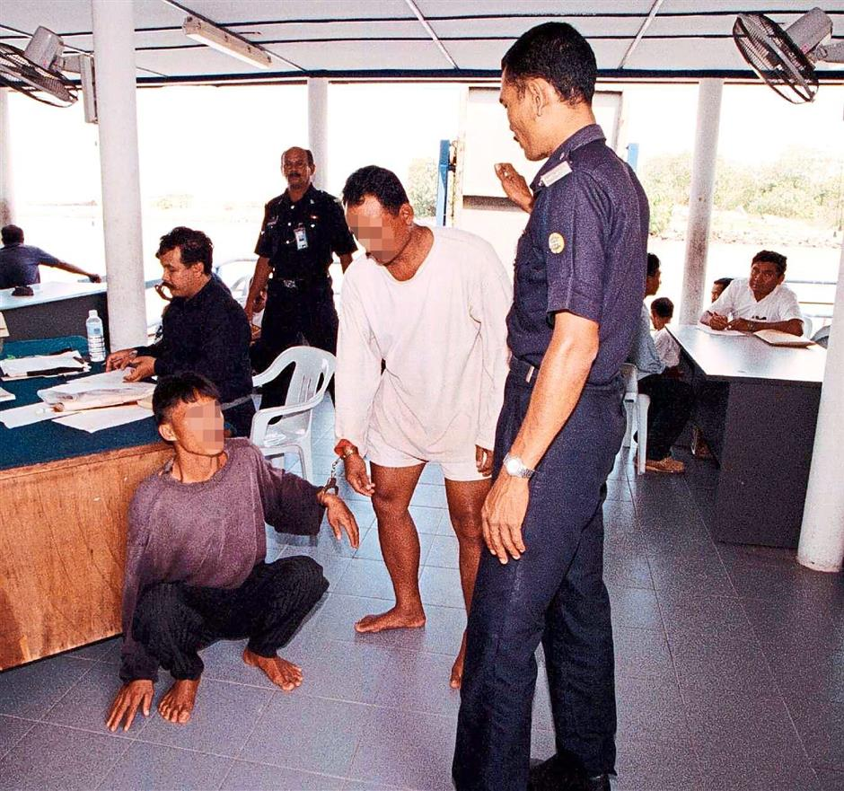 Former hotspot: A filepic of a marine police officer questioning two suspects caught for smuggling illegal immigrants in Malacca.