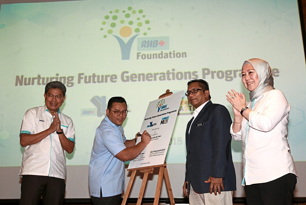 Amirudin (second from left) launching RHB X-Cel and RHB MoneyMaster. With him are (from left) Khairussaleh, Izehari and Norazzah.