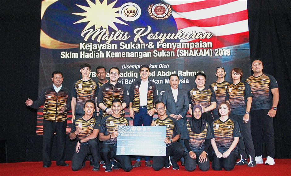 Proud: Youth and Sports Minister Syed Saddiq Syed Abdul Rahman (standing fourth from left), his deputy Steven Sim (third from left) and Olympic Council of Malaysia president Datuk Seri Norza Zakaria (fifth from right) with the para athletes in Bukit Jalil yesterday. — SHAHRIL ROSLI / The Star