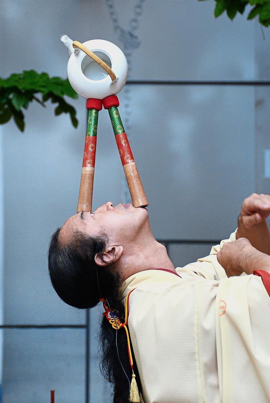 Senmaru displaying his skills balancing a ceramic teapot atop drumsticks.