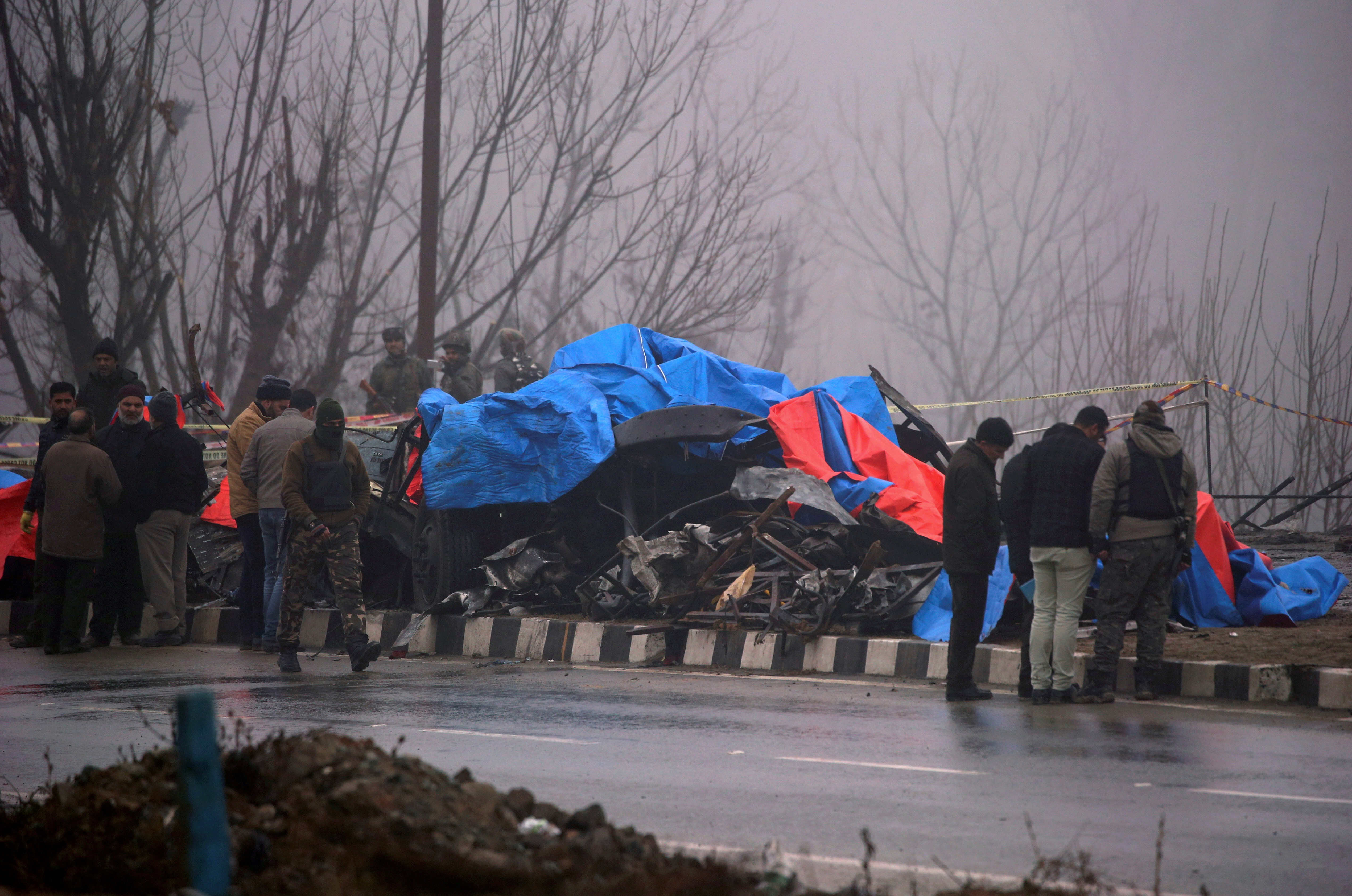 FILE PHOTO: Forensic officials inspect the wreckage of a bus after a suicide bomber rammed a car into the bus carrying Central Reserve Police Force (CRPF) personnel on Thursday, in Lethpora in south Kashmir's Pulwama district, February 15, 2019. REUTERS/Danish Ismail/File Photo