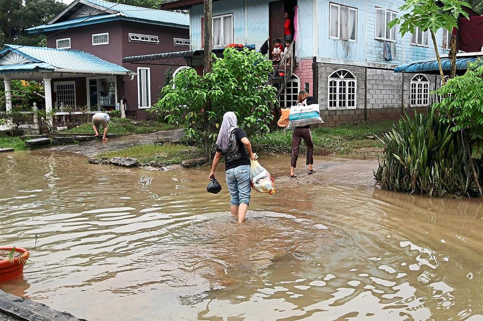 VILLAGERS KAMPUNG BATU KITANG GOING BACK TO THEIR HOUSE AFTER FLOOD ZULAZHAR SHEBLEE / THE STAR