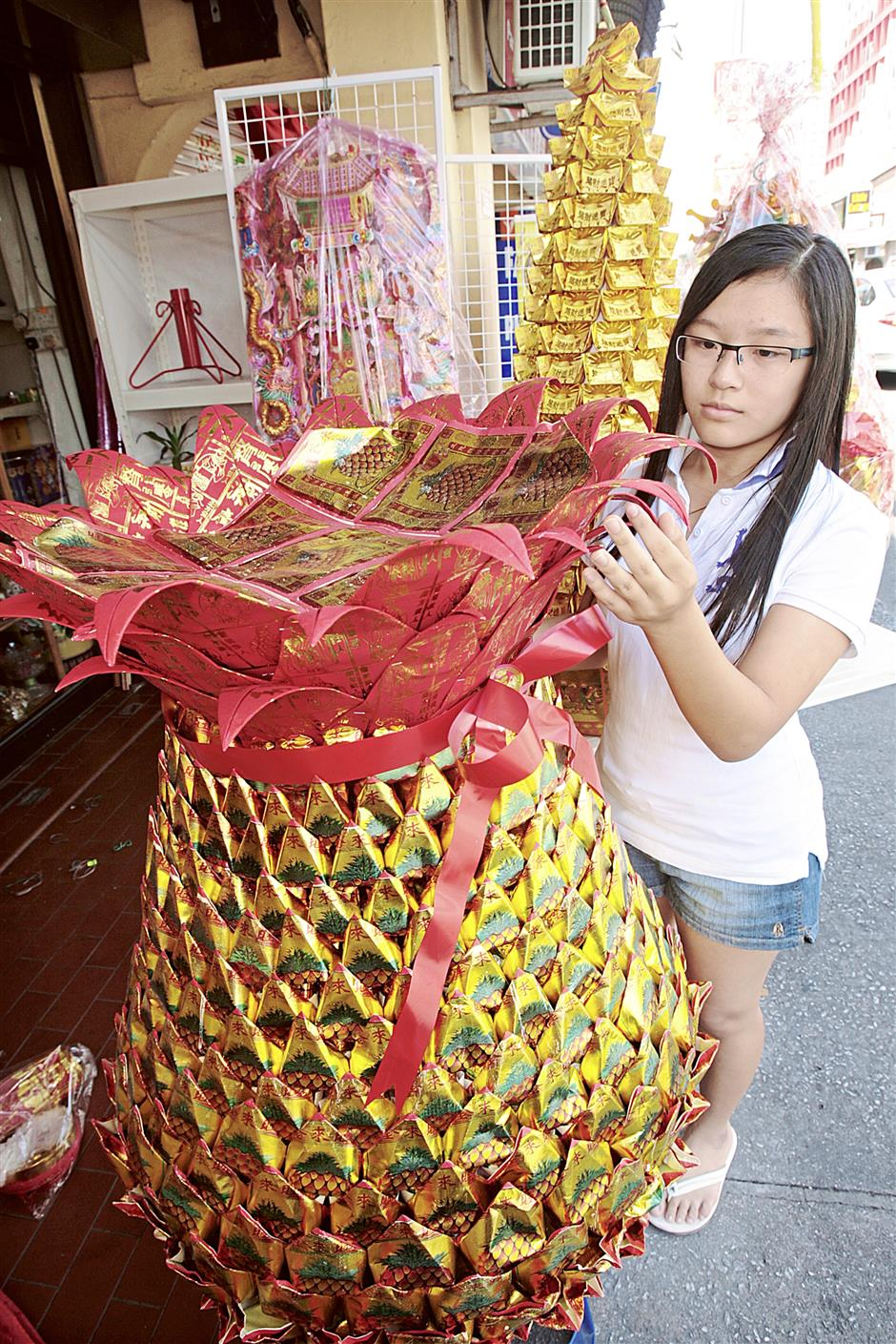 Student Jocelyn Teh, the daughter of prayer paraphernalia trader G.H.Teh, showing a pineapple-shape 'Thnee Kong Poh