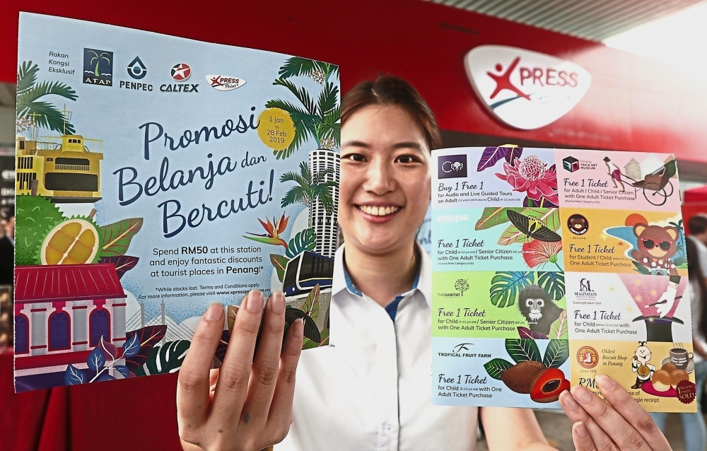 PenPec marketing development manager Nicole Lim Pei Xuan showing the discount vouchers customers will receive at selected Caltex stations.