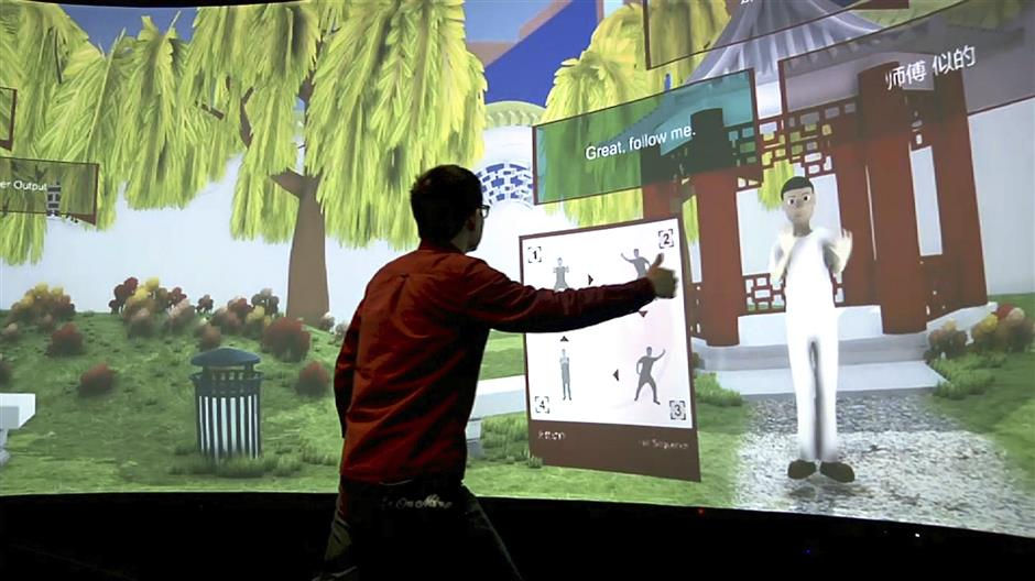 In this Aug. 22, 2018 image taken from video, Rensselaer Polytechnic Institute graduate student Xiangyang Mou practices tai chi with an avatar in a campus studio at Rensselaer Polytechnic Institute in Troy, N.Y. The 'Mandarin Project' is a joint venture of RPI and IBM. Cognitive and Immersive Systems Laboratory researchers are developing a sort of smart room that can understand students' words, answer their questions and perceive their gestures. (AP Photo/Michael Hill)