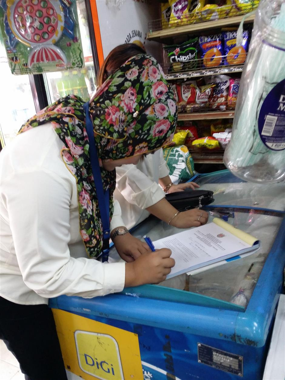 An MBSA officer writing a report after seizing some expired goods at one of the stores.