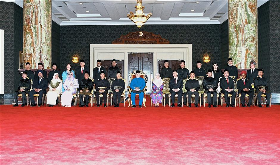 New era: Sultan Muhammad V (centre) posing for a photo with Dr Mahathir and the new Cabinet after the swearing-in ceremony at Istana Negara. u2014 Bernama