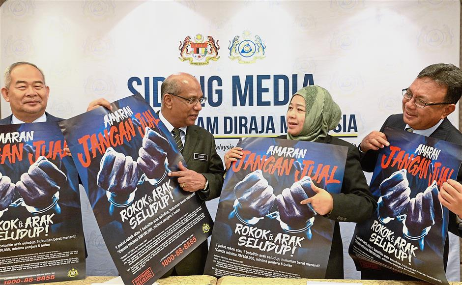 Poster war: (From left) Customs deputy director-general Datuk Dr Zukefli Ibrahim, ufeffSubromaniamufeff, Customs deputy director-general (enforcement and compliance) Datuk Azimah Abd Hamid and Customs corporate planning division deputy director Shafif Aziz at the press conference on alcohol and cigarette smuggling.